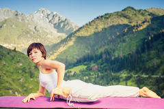 Inspired asian woman doing exercise of yoga at mountain range Royalty Free Stock Image