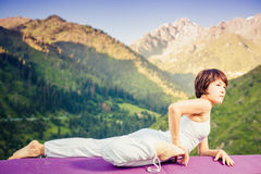 Inspired asian woman doing exercise of yoga at mountain range Stock Photo