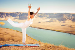 Inspired asian woman doing exercise of yoga at mountain range. Of Kazakhstan. She dressed in white sportswear Stock Images