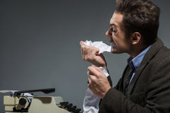 Inspired author biting crumpled paper Stock Image