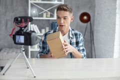 Inspired blogger making a video for his followers. My favourite work. Attractive alert young well-built man talking and opening his box while making a video Stock Photos