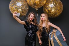 Inspired blonde woman holding big blue present and smiling at birthday party. Charming girl in black dress making selfie. Inspired blonde women holding big blue stock image
