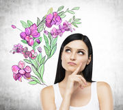 An inspired brunette is dreaming about summer flowers. Stock Photo