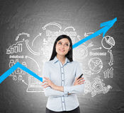 Inspired businesswoman and blue graph, icons. Portrait of an inspired businesswoman with black hair and a marker. She is standing near a blackboard with a blue Royalty Free Stock Photos