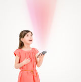 Inspired child with smartphone. Inspired cute little girl in red dress looking up on ray of light from mobile phone in her hand. Isolated on beige background Stock Photography