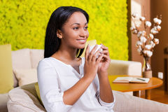 Inspired with cup of fresh coffee. Cheerful young African woman drinking coffee and looking away while sitting at the chair at home Stock Photos