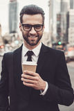 Inspired with cup of fresh coffee. Confident young man in full suit holding coffee cup and looking at camera with smile while standing outdoors with cityscape Royalty Free Stock Photography
