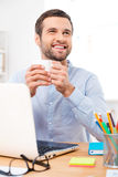 Inspired with cup of fresh coffee. Handsome young man holding a cup of coffee and looking away while sitting at his working place Royalty Free Stock Photos