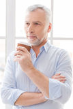 Inspired with cup of fresh coffee. Thoughtful grey hair senior man in shirt holding coffee cup and looking away while standing in front of the window Royalty Free Stock Photo