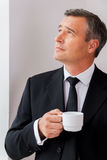 Inspired with cup of fresh coffee. Thoughtful mature man in formalwear holding coffee cup and looking away while standing near window Stock Photos
