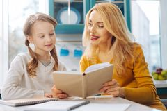 Inspired daughter reading with her mother. Funny reading. Pretty inspired blond slim mother smiling and looking at her daughter and while sitting at the table Royalty Free Stock Photo