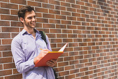 Inspired designer making sketch outdoors. Talented male artist is drawing on street. He is holding folder of paper and laughing. Man is standing near wall and Royalty Free Stock Images