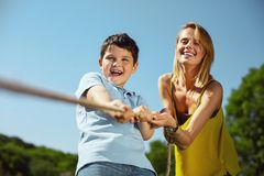 Inspired family pulling a rope in the park. Great activity. Content loving mother helping her son while he pulling a rope with his sister Royalty Free Stock Images