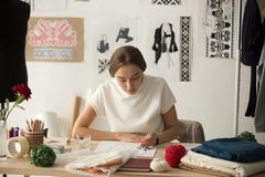 Inspired fashion designer working in studio drawing new collecti. Inspired woman fashion designer drawing sketches with brush at workplace, needlewoman works in Stock Photography