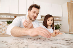 Inspired father and daughter doing a jigsaw puzzle together Royalty Free Stock Photography