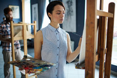 Inspired Female Artist in Class. Portrait of inspired young women painting picture on easel standing in row of students in art class Royalty Free Stock Photos