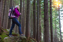 Inspired Female Hiker Staying on Stone in Forest. Lady Outdoor Hiker Staying on Stone in Dense Forest Smiling Inspired Face with Backpack and Walking Poles Stock Image