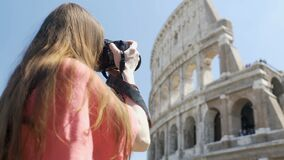 Inspired female photographer taking picture of Colosseum amphitheater in Rome stock footage