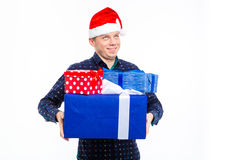 Inspired foretasted young man in santa claus hat holding presents Royalty Free Stock Photography