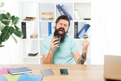 Inspired and full of energy. Office life rhythm. Regular office day. Man bearded guy headphones sit office listen music. Sing song. Worker with coffee cup begin stock images