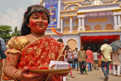 Inspired Girl. A beautiful little girl inspired by the festive surroundings she smear and play with vermilion during the traditional ceremony of Durga Puja Royalty Free Stock Image