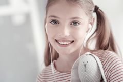 Inspired girl with headset and her toy. Being a teenager. Attractive exuberant grey-eyed lovely girl with pig-tails smiling and holding a toy while wearing a Stock Images