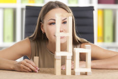 Inspired girl is playing with wood bricks. Inspired woman in beige is playing with wooden bricks at her workplace in a white office. Concept of a break Royalty Free Stock Photos
