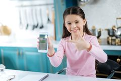 Inspired girl pointing at the screen of her phone. Look here. Pretty content dark-eyed girl smiling and holding her phone and pointing at the screen while Royalty Free Stock Photo