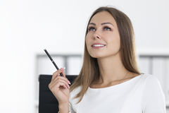 Inspired girl in white in office. Portrait of an inspired woman wearing white clothes and looking upwards thinking about current task Royalty Free Stock Images
