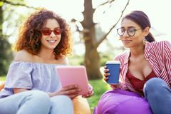 Inspired girls talking and relaxing. Our friendship. Delighted curly-haired women holding a tablet and talking with her friend Stock Images