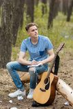Inspired guitarist creates nature hiking concept. Inspired guitarist creates new song. Nature hiking concept. Active lifestyle. Working process Royalty Free Stock Images