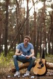 Inspired guitarist creates nature hiking concept. Inspired guitarist creates song. Nature hiking concept. Active lifestyle. Working process Royalty Free Stock Images