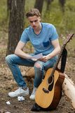 Inspired guitarist creates nature hiking concept. Inspired guitarist creates new song. Nature hiking concept. Active lifestyle. Working process Stock Photography