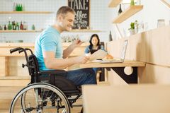 Inspired handicapped man working from a cafe. Distance working. Attractive inspired handicapped men sitting in a wheelchair and holding a sheet of paper and a Royalty Free Stock Photo