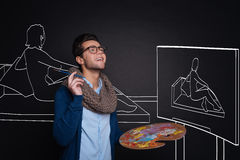 Inspired handsome man holding palette and painting. royalty free stock photo