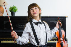 Inspired and happy girl holding a violin indoor Stock Photos