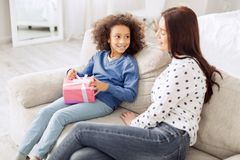 Inspired little girl holding her gift. Congratulations. Attractive content curly-haired girl smiling and holding her gift while looking at her mother sitting Royalty Free Stock Photography