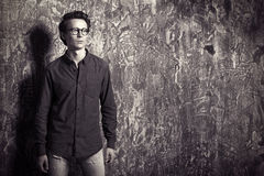 Inspired look. Portrait of young man in casual jeans clothes and spectacles posing over grunge background. Men`s beauty, fashion. Optics style Royalty Free Stock Photo