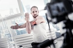 Inspired male blogger recording stretching. Right beginning. Handsome bearded male blogger training on mat board while recording video and stretching Stock Photo