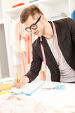 Inspired male tailor designing new clothing Stock Image