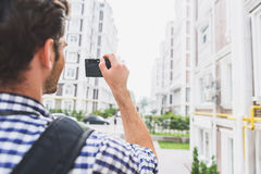 Inspired male tourist using camera in city Stock Photo