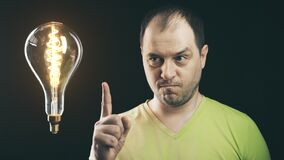 Inspired man and big shining light bulb. Insight or idea concepts