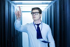 Inspired man pointing his finger. Interesting work. Handsome inspired man working in a data center and pointing with his finger Royalty Free Stock Image