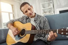 Inspired man relaxing and playing the guitar. My hobby. Good-looking alert well-built man smiling and playing the guitar while sitting on the couch Royalty Free Stock Photo