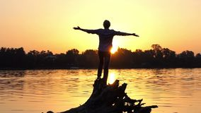 Inspired man stands on tree roots on a lake bank in slo-mo. An impressive view of a young man who stands on tree roots and keeps his hands aside on a forest lake stock video