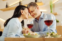 Inspired man and woman having dinner and drinking wine. Red wine. Pretty content disabled women and an attractive smiling well-built men sitting in a cafe with Stock Photography