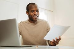 Inspired man working on his startup. Startup. Attractive vigorous dark-eyed bearded afro-american man smiling and working on the laptop and holding a sheet of Stock Photography