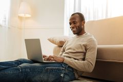 Inspired man working from home. Nice day. Exuberant bearded afro-american man smiling and working on the laptop and typing while sitting on the floor near the Royalty Free Stock Photo