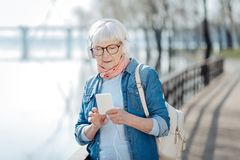 Inspired mature woman listening to music. Maturity. Delighted aged woman listening to music while walking in the park Royalty Free Stock Image