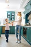 Inspired mother and daughter dancing in the kitchen. I treasure you. Pretty caring fair-haired young mother smiling and holding hands with her daughter while Royalty Free Stock Photo